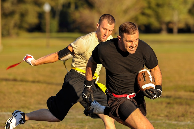 Senior Airman Nathan Hooven, 437th Aircraft Maintenance Squadron dedicated crew chief, grabs the flag off of Senior Airman Garrett Busk, 628th Civil Engineer Squadron HVAC technician, during an intramural football game Oct. 21, 2014, at Joint Base Charleston, S.C. The 628th Force Support Squadron runs multiple intramural leagues to include flag football, softball and volleyball throughout the year. (U.S. Air Force photo/Staff Sgt. Renae Pittman)