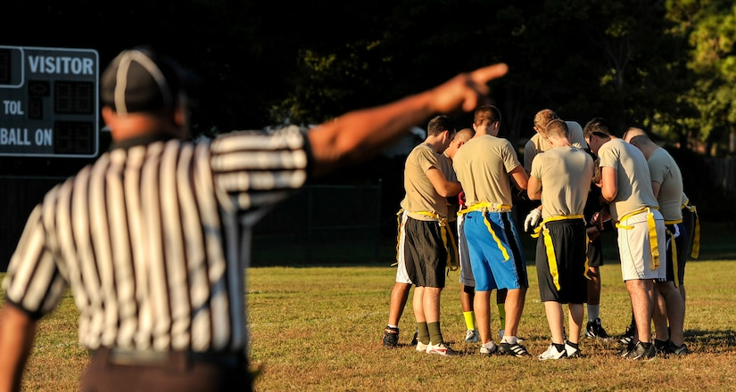 Referee Sam Mathis directs the 437th Aircraft Maintenance Squadron intramural flag football team to take their positions during the Air Base intramural football season opener Oct. 21, 2014, at Joint Base Charleston, S.C. The 437th AMXS lost to the 628th Civil Engineer Squadron 14 to 24. Each Air Base intramural team will play 13 games prior to the championship scheduled for early December. (U.S. Air Force photo/Staff Sgt. Renae Pittman)