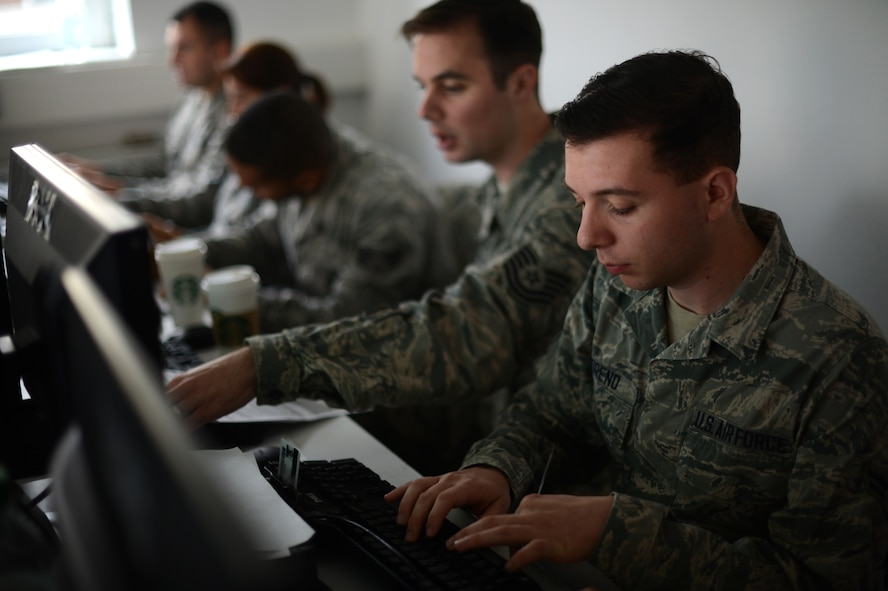 Members of the 52nd Medical Group transcribe statistics into computers at the Skelton Memorial Fitness Center at Spangdahlem Air Base, Germany, Oct. 23, 2014. Vaccine recipients needed to fill out paperwork prior to the event for accountability purposes. The 52nd MDG technicians uploaded the information to allow a real-time report of the Airmen to unit commanders. (U.S. Air Force photo by Senior Airman Gustavo Castillo/Released)