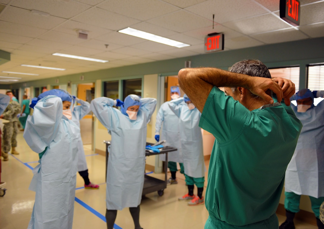 """Navy Cmdr. James Lawler, right, a member of the DoD medical support team training, leads a group of students in removing their personal protective equipment during training at the San Antonio Military Medical Center in San Antonio, Texas, Oct. 24, 2014. The students are part of a 30-person team designated for """"prepare to deploy"""" status in the event of an Ebola crisis in the U.S. DoD photo by Army Sgt. 1st Class Tyrone C. Marshall Jr."""