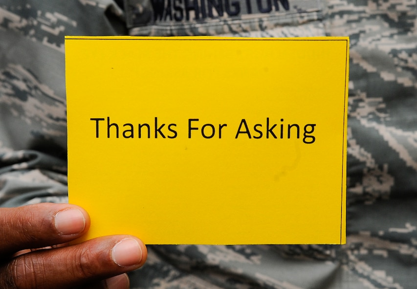 "A medical professional from the 1st Special Operations Medical Group holds up a ""Thanks for Asking"" card on Hurlburt Field, Fla., Oct. 23, 2014. People received this card if they asked simulated domestic violence victims about their bruises and black eyes. (U.S. Air Force photo/Airman 1st Class Andrea Posey)"