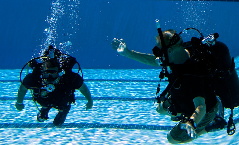"""Michael Gray, right, 24th Special Operations Wing water operations instructor, tests Johnnie Yellock's, left, retired Staff Sgt. and 23rd Special Tactics Squadron combat controller, ability to move through water during SCUBA-Pool Emergency Procedures training on Hurlburt Field, Fla. Oct. 21, 2014. """"Johnny's situation does not allow the use of swim fins,"""" said Gray. """"He pretty much follows the same guidelines used for paraplegics."""" (U.S. Air Force photo/Senior Airman Kentavist P. Brackin)"""