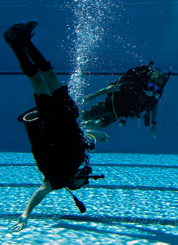 Johnnie Yellock, left, retired Staff Sgt. and 23rd Special Tactics Squadron combat controller, attempts vertical swimming while Michael Gray, right, 24th Special Operations Wing water operations instructor, looks on during SCUBA-Pool Emergency Procedures training on Hurlburt Field, Fla. Oct. 21, 2014. One of challenges Yellock had during the refresher training was maintaining his balance in water without the usual support and propulsion of his legs.(U.S. Air Force photo/Senior Airman Kentavist P. Brackin)