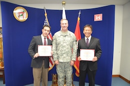 U.S. Army Corps of Engineers, Japan District Commander Col. John Hurley (center) shown with James Kelly (left) and Victor Michimoto (right), recent graduates of Pacific Ocean Division's USACE Leadership Development Level 3 Program. Kelly and Michimoto were honored during a ceremony Oct. 15 that linked participants by video teleconference from the division headquarters at Fort Shafter, Hawaii. Through its ULDP program, POD is developing civilian leaders who will encourage innovation, teamwork and partnerships to maximize the organization efficiency and effectiveness. Congratulations James and Victor!