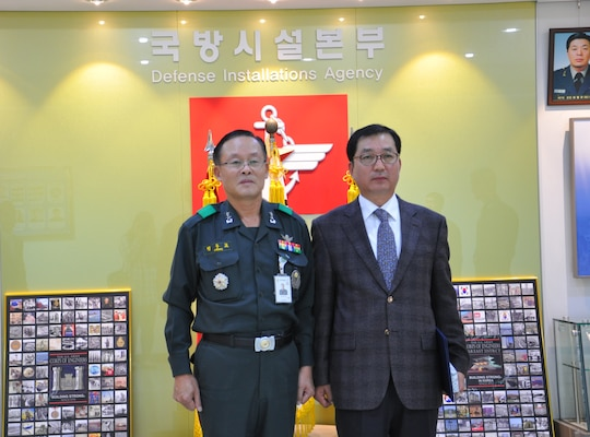 Republic of Korea Maj. Gen. Chung Joo Kyo, commander of the Ministry of National Defense-Defense Installations Agency presents a certificate of commendation to Chang U-ik, Humphreys area office safety and occupational health specialist.