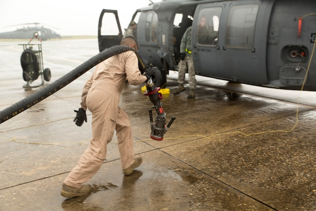 Cpl. Eduardo Bahena, a semitrailer refueler operator with Marine Wing Support Squadron 171, carries a hose to refuel an HH-60G Pave Hawk during the Korean Marine Exchange Program 14-13, Oct. 20, 2014, on Osan Air Base, Republic of Korea. The program's goals are to increase the combat readiness of Marine Aircraft Group 12, improve its operating skills as a Marine Air-Ground Task Force and enhance joint and combined integration with the U.S. Air Force and ROK Marine Corps. KMEP 14-13 is a multinational exercise that focuses on the integration of aviation and ground assets within the construct of a traditional Combined Arms Live Fire Exercise. Supporting assets include, but are not limited to, Marine Aviation Logistics Squadron 12 and MWSS-171.