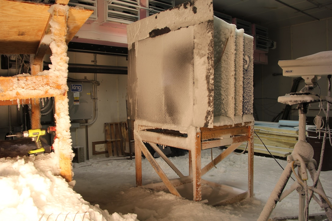 In ERDC-CRREL's Materiel Evaluation Facility (MEF), which has snow-making, freezing-rain, and sleet-making capabilities, researchers evaluate the shedding ability of a mechanical louver system in a variety of snow and sleet conditions.
