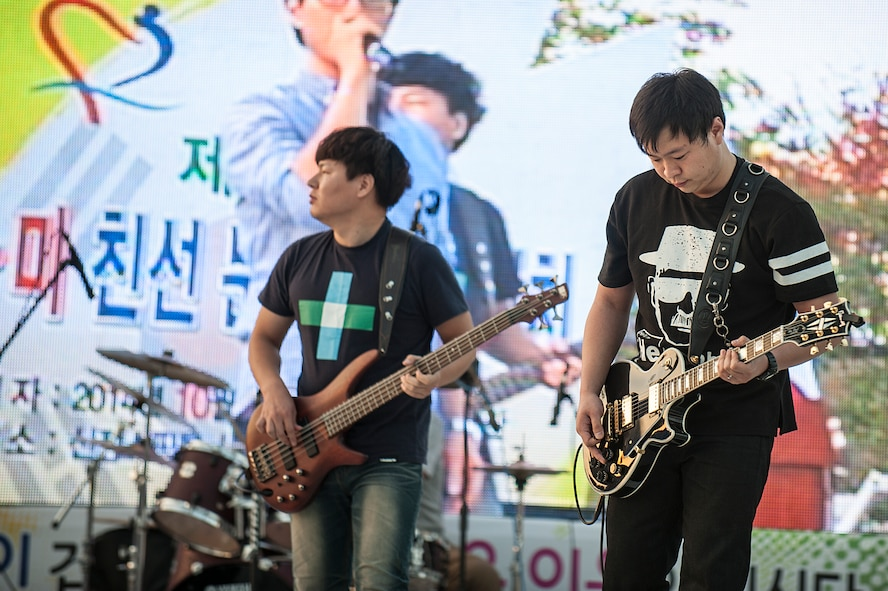Members of a Korean band play guitars during the 11th Korean American Friendship Cultural Festival at the Songtan Entertainment District, Republic of Korea, Oct. 25, 2014. A variety of different groups entertained the festival audience with a range of musical performances. (U.S. Air Force photo by Senior Airman Matthew Lancaster)