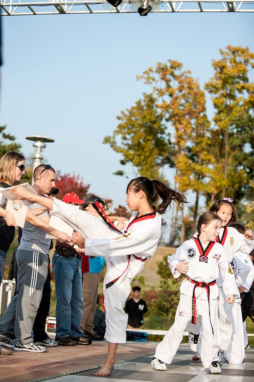 Members of a local Taekwondo group demonstrate their skills during the 11th Korean American Friendship Cultural Festival at the Songtan Entertainment District, Republic of Korea, Oct. 25, 2014. The featured American and Korean stage performers, martial arts demonstrations, cultural food and entertainment booths. (U.S. Air Force photo by Senior Airman Matthew Lancaster)