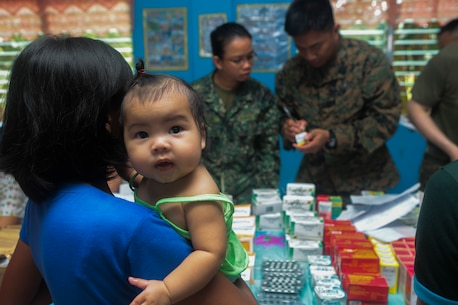 A mother picks up prescriptions with her daughter in hand during a community health engagement program leading up to Amphibious Landing Exercise (PHIBLEX) 15 in Palawan, Philippines, Sept. 19, 2014. PHIBLEX is an annual, bilateral training exercise conducted by the Armed Forces of the Philippines, U.S. Marines and Navy to strengthen interoperability across a range of capabilities to include disaster relief and contingency operations. (U.S. Marine Corps photo by Pfc. Matthew Casbarro/Released