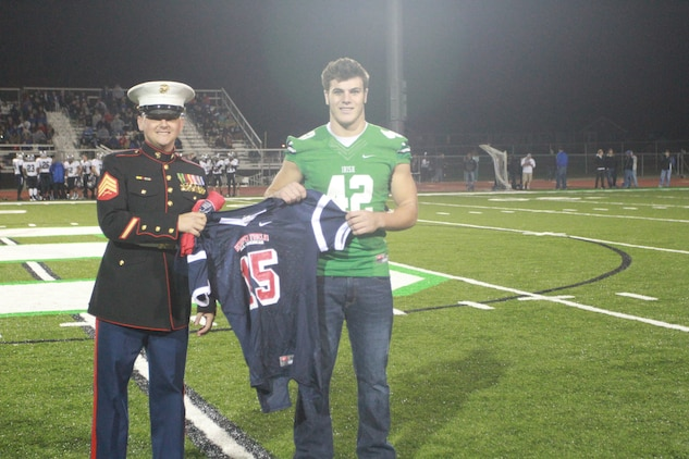 Nick Conner, a Dublin Scioto High School linebacker, is presented with a jersey by U.S. Marine Corps Sgt. Nikolas Cimmarrusti, a recruiter for the Dublin, Ohio, area, during a  ceremony after the first quarter at the Dublin Scioto Football Stadium Oct. 24, 2014. Conner has been officially selected to play in the Marine Corps Semper Fidelis All American Bowl, which will be held Jan. 4, 2015 in Carson, California. (U.S. Marine Corps photo by Sgt. Tyler Hlavac/Released)