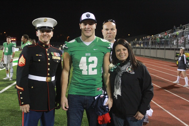 Nick Conner, a linebacker with the Dublin Scioto High School football team, poses for a photo alongside his parents, Scott and Renee, and U.S. Marine Corps Sgt. Nikolas Cimmarrusti, a Marine recruiter for the Dublin, Ohio, area. Conner has been officially selected to play in the Marine Corps Semper Fidelis All American Bowl, which will be held Jan. 4, 2015 in Carson, California. (U.S. Marine Corps photo by Sgt. Tyler Hlavac/Released)