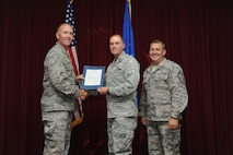 Capt. James Morrison, 33rd Maintenance Squadron, is presented the Gen. Lew Allen, Jr. Trophy, officer category award from Col. Todd Canterbury, 33rd FW commander, and Chief Master Sgt. Scott Berge, 33rd FW command chief, on Eglin Air Force Base, Fla., Oct 17, 2014. Morrison acted as the 58th Aircraft Maintenance Unit officer in charge during this quarter and is now the maintenance operations officer for the 33rd Maintenance Squadron. (U.S. Air Force photo/Staff Sgt. Marleah Robertson)