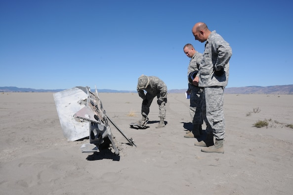 From Right: Maj. Lucas Ritter the casualty assistance officer, Maj. Ryan Bartholomew, the base historian and Staff Sgt. Brandon Stroh of security forces investigate newly exposed wreckage from WWII aircraft on the dry lakebed of Goose Lake, Oct. 3, 2014. Current drought conditions have drawn the water level well below parts of the lakebed for the first time. The aircraft flights originated at Kingsley Field for training and unfortunately never returned to the base.  (U.S. Air National Guard photo by Tech. Sgt. Jefferson Thompson)
