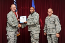 Lt. Col. Rodrick Webb, 33rd Maintenance Group deputy commander, accepts the 33rd FW civilian of the quarter category III award on behalf of Ms. Keisha Mitchell, 33rd MXG resource advisor, from Col. Todd Canterbury, 33rd FW commander, and Chief Master Sgt. Scott Berge, 33rd FW command chief, on Eglin Air Force Base, Fla., Oct 17, 2014. Mitchell guided the 33rd MXG through a successful close-out by utilizing $681K in funding resulting in a flawless execution. (U.S. Air Force photo/Staff Sgt. Marleah Robertson)