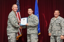 Capt. Brian Saari, 33rd Operations Group chief of F-35 intelligence formal training unit, accepts the 33rd FW civilian of the quarter category II award on behalf of Terry Youngblood, 33rd OG special security representative, from Col. Todd Canterbury, 33rd FW commander, and Chief Master Sgt. Scott Berge, 33rd FW command chief, on Eglin Air Force Base, Fla., Oct 17, 2014. Youngblood renovated the wing's special compartmented information database by revalidating the requirements for 49 billets and reviewed all required justifications which guaranteed program integrity. (U.S. Air Force photo/Staff Sgt. Marleah Robertson)