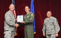 Lt. Col. Eric Smith, 33rd Operation Support Squadron commander, accepts the 33rd FW field grade officer of the quarter award on behalf of Maj. Trevor Hollis, 33rd OSS senior intel officer, from Col. Todd Canterbury, 33rd FW commander, and Chief Master Sgt. Scott Berge, 33rd FW command chief, on Eglin Air Force Base, Fla., Oct 17, 2014. Hollis stood up the first and only F-35 intelligence formal training unit. By driving 386 training hours, two beta classes and graduating 16 students, Hollis's actions have pioneered the next 40 years of F-35 intelligence support. (U.S. Air Force photo/Staff Sgt. Marleah Robertson)