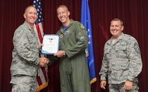 Lt. Col. Brad Turner, 33rd Fighter Wing chief of safety, accepts the 33rd FW company grade officer of the quarter award on behalf of Capt. Daniel Haley, 33rd FW flight safety officer, from Col. Todd Canterbury, 33rd FW commander, and Chief Master Sgt. Scott Berge, 33rd FW command chief, on Eglin Air Force Base, Fla., Oct 17, 2014. Haley is recognized for being the lead advisor to the accident and safety investigation boards for the first F-35A Lightning II Class-A mishap. His actions were lauded by Gen. Robin Rand, Air Education and Training Command commander. (U.S. Air Force photo/Staff Sgt. Marleah Robertson)