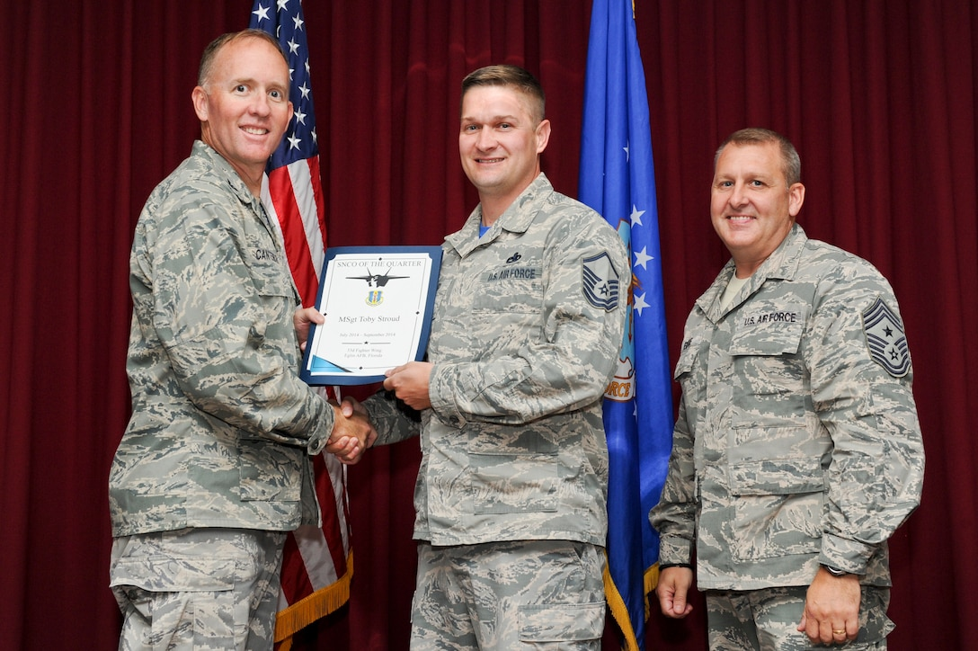 Master Sgt. Toby Stroud, 33rd Maintenance Group aircraft maintenance section chief, is presented the 33rd Fighter Wing senior non-commissioned officer of the quarter award from Col. Todd Canterbury, 33rd FW commander, and Chief Master Sgt. Scott Berge, 33rd FW command chief, on Eglin Air Force Base, Fla., Oct 17, 2014. Stroud is recognized for organizing a current F-35 noise study survey by coordinating a 10 member team and collecting data on two aircraft, resulting in a program-wide noise survey update. (U.S. Air Force photo/Staff Sgt. Marleah Robertson)