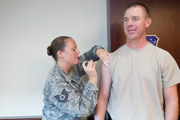 Tech. Sgt. Sara McCoskey, 45th Aerospace Medical Squadron independent duty medical technician, administers an influenza vaccine to Chief Master Sgt. Craig Neri, 45th Space Wing command chief, Oct. 27, 2014, at Patrick Air Force Base, Fla. The influenza vaccine is now available at the 45th Medical Group Allergy and Immunization Clinic. (U.S. Air Force photo/Matthew Jurgens/Released)