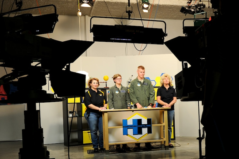 Janae Passalaqna, far left, a teacher at East High School in Pueblo, Colo., and Betty Lee, far right, a retired teacher, listen in as Cadets 3rd Class Casey Evans and Warren Metcalf explain the specifics of 3D printing at the Public Broadcasting Service at Colorado State University – Pueblo, Oct. 24, 2014. The cadets helped Passalaqna and Lee host Homework Hotline, which allows school-aged children to call in with homework-related questions. (U.S. Air Force photo/Airman 1st Class Rachel Hammes)