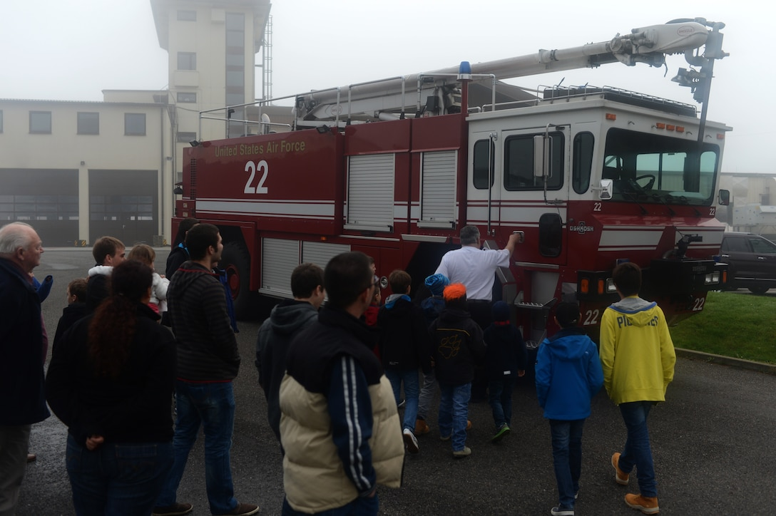 Junior firefighters from Luxembourg and their families tour a fire truck at the 52nd Civil Enginner Squadron fire station on Spangdahlem Air Base, Germany, Oct. 27, 2014. The Spangdahlem fire department hosts tours year-round and facilitates approximately one tour per week during the summer months. (U.S. Air Force photo by Senior Airman Gustavo Castillo/Released)
