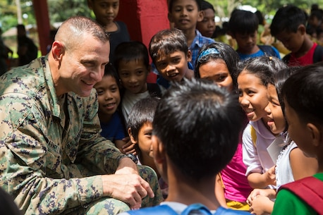 U.S. Marine Corps Col. John Armellino, chief of staff, 3rd Marine Expeditionary Brigade, speaks with local Philippine children during a community health engagement at San Rafael High School leading up to Amphibious Landing Exercise (PHIBLEX) 15 in Palawan, Philippines, September 26, 2014. PHIBLEX is an annual, bilateral training exercise conducted by the Armed Forces of the Philippines, U.S. Marines and Navy to strengthen interoperability across a range of capabilities to include disaster relief and contingency operations. (U.S. Marine Corps photo by Pfc. Matthew Casbarro/Released)