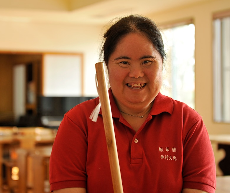 Yoshie Nakamura, welfare employment center employee, poses for a picture while sweeping at the Fuyo-Kan, welfare employment center, Oct. 28, 2014. Nakamura will be participating in her fourth Kadena Special Olympics for 50 meter and ground golf. Nakamura is looking forward to aim higher performance at this KSO. (U.S. Air Force photo by Naoto Anazawa/Released)