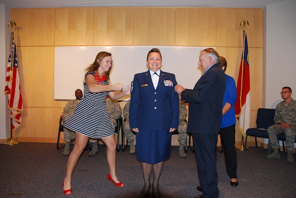 U.S. Air National Guard Chief Master Sgt. Angela Zephier, superintendent of the 156th Weather Flight, gets the rank of Chief tacked on by daughter Sarah, and father, retired Chief Warrant Officer (4) Larry Deal, during her promotion ceremony held at the 145th Combat Operations Group, New London, N.C. October 4, 2014. (U.S. Air National Guard photo by Master Sgt. Matthew Ciampa, 145th Weather Flight/Released)