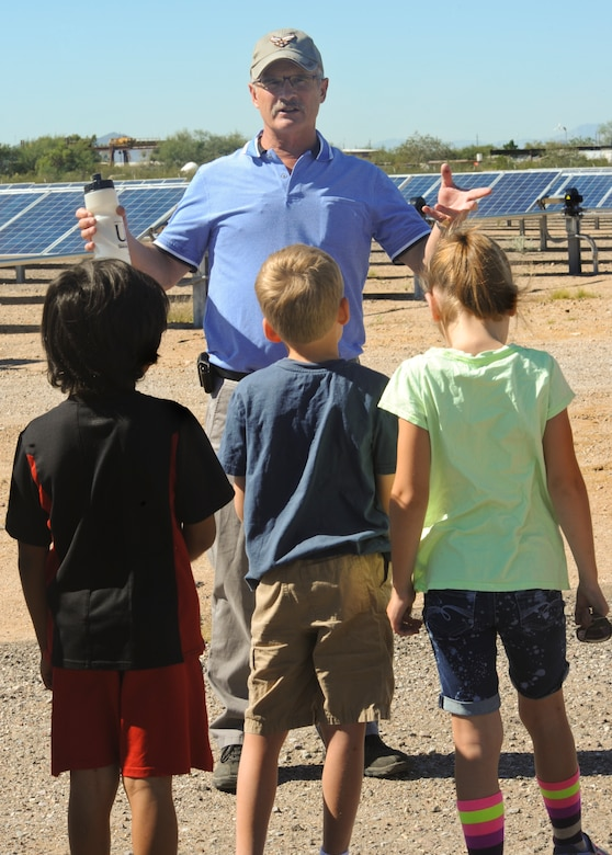 Greg Nobel, 355th Fighter Wing energy manager, explains what solar panels do to children from Borman Elementary School around the 16.4 megawatt Solar Array to celebrate Energy Action Month at Davis-Monthan Air Force Base, Ariz., Oct. 22, 2014. The 355th Civil Engineering Squadron partnered with local schools to help educate the students on benefits of conserving energy. (U.S. Air Force photo by: Staff Sgt. Angela Ruiz/Released)