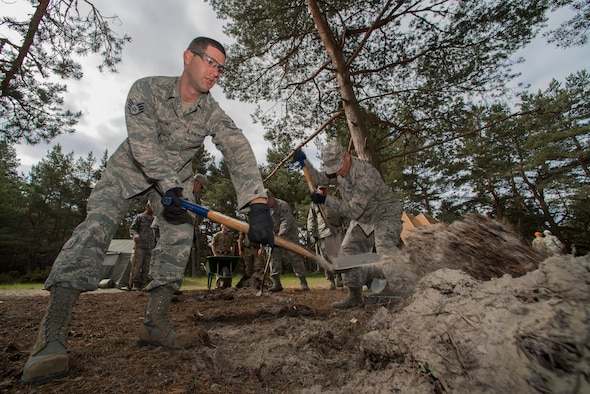 U.S. Air Force Staff Sgt. William Bryant, 140th Civil Engineering Squadron, Colorado Air National Guard, removes soil from an area that will later become a barbecue griller, during a deployed for training trip, known as Exercise Flying Rose at Kinloss Barrack in Forres, Moray, Scotland, United Kingdom, Jun. 11, 2014. Over 40 members of the 140th CES are in Scotland for their annual training and are accomplishing five construction projects that will improve several areas around Kinloss Barracks, during Exercise Flying Rose hosted by the British Army before returning back to Colorado later this month. (U.S. Air National Guard photo/Tech. Sgt. Wolfram M. Stumpf)