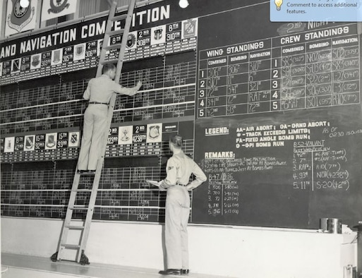 "Two Airmen of the 807th Air Base Group Comptroller's staff posting the master scoreboard in the ""Jumbo Hangar"" at March Air Force Base, California, during the 10th annual Strategic Air Command Bombing and Navigation Competition, Oct. 13-18, 1958. (U.S. Air Force Photo)"