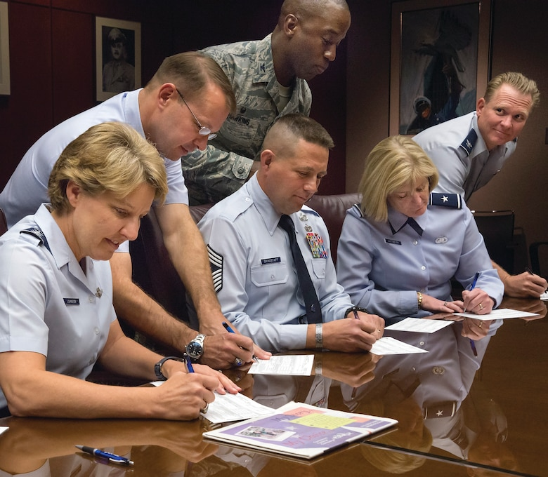 Academy Superintendent Lt. Gen. Michelle D. Johnson (left) and other senior Academy leaders sign their Combined Federal Campaign donation forms here Oct. 22, 2014. (U.S. Air Force photo/Liz Copan)