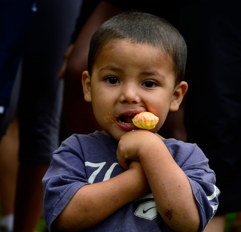 A young boy chews on a lollipop given to him by one of the Chapel Hike volunteers in Potrerillos, Siguatepeque, Honduras, Oct. 25, 2014.  As part of the 57th Chapel Hike, more than 130 members assigned to Joint Task Force-Bravo laced up their hiking boots and trekked almost four miles up a mountain to help deliver over 3,500-pounds of donated dry goods to villagers in need. (U.S. Air Force photo/Tech. Sgt. Heather Redman)