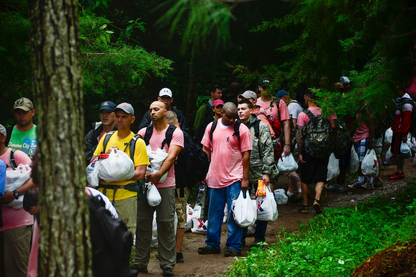Members from Joint Task Force-Bravo, wait in line to give their bags of donated food and clothes to villagers in Potrerillos, Siguatepeque, Honduras, Oct. 25, 2014.  As part of the 57th Chapel Hike, more than 130 members assigned to Joint Task Force-Bravo laced up their hiking boots and trekked almost four miles up a mountain to help deliver over 3,500-pounds of donated dry goods to villagers in need. (U.S. Air Force photo/Tech. Sgt. Heather Redman)