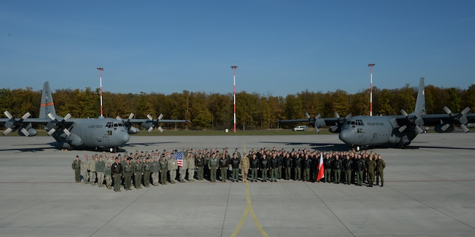 U.S. Air Force Airmen assigned to the 182nd Airlift Wing, Illinois Air National Guard, Peoria, Ill., and Detachment 1, 52nd Operations Group, from Lask Air Base, Poland, and Polish airmen assigned to the33rd Transportation Air Base pose for a group photo after a training mission Oct. 24, 2014, at Powidz Air Base, Poland. The 182nd AW supported rotation 15-1 hosted by the Aviation Detachment. The U.S. Air Force's forward presence in Europe allows allies and partners to develop and improve ready air forces capable of maintaining regional security. (U.S. Air Force photo by Airman 1st Class Dylan Nuckolls/Released)