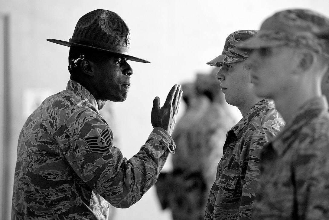 A military training instructor gives instruction to a trainee and his wingman during a formation at Joint Base San Antonio - Lackland, Texas. (U.S. Air Force photo/Master Sgt. Jeffrey Allen)