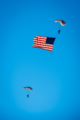 Retired Marine Cpl. William Kyle Carpenter, a Medal of Honor recipient, parachutes down with the United States Flag during the opening ceremony of Sunday's 39th Annual Marine Corps Marathon. Carpenter, who survived after jumping atop an enemy grenade in Afghanistan in 2010 to save a fellow Marine, parachuted in before running the marathon. He finished with a time of 5:07:45.