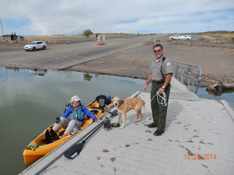 COCHITI LAKE, N.M., -- Park Ranger Adrian Glass holds the leash of the dog picked up by the kayaker, Oct. 28.