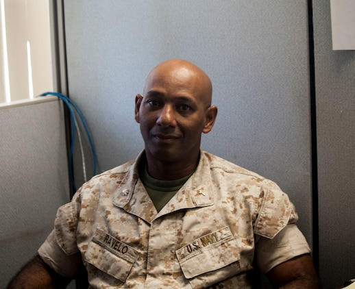 U.S. Navy Cmdr. Samuel Ravelo poses for a photo at his desk aboard Camp Pendleton, Calif., Oct. 28, 2014. Commander Ravelo is the chaplain for the 15th Marine Expeditionary Unit. (U.S. Marine Corps photo by Cpl. Elize McKelvey/Released)