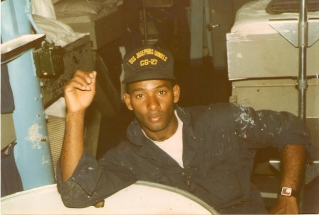 U.S Navy Seaman Samuel Revelo takes a break after a hot day aboard the USS Josephus Daniels. (Courtesy photo circa 1986/Released)