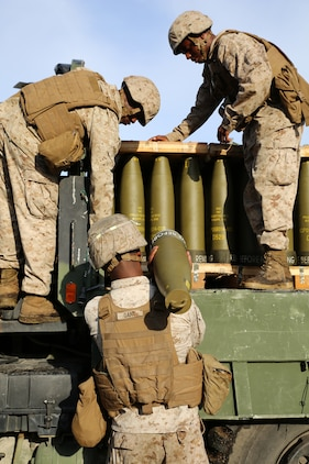 A cannoneer with Battery A, Ground Combat Element Integrated Task Force, receives an M777A2 Lightweight Howitzer round for the Gun 3 ammo pit prior to conducting live-fire artillery missions at Marine Corps Base Camp Lejeune, North Carolina, Oct. 30, 2014. Marines of Battery A conducted a live-fire artillery shoot, Oct. 28-30, 2014. From October 2014 to July 2015, the GCEITF will conduct individual and collective level skills training in designated ground combat arms occupational specialties in order to facilitate the standards based assessment of the physical performance of Marines in a simulated operating environment performing specific ground combat arms tasks. (U.S. Marine Corps photo by Sgt. Alicia R. Leaders/Released)