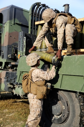 Lance Cpl. Vicki A. Harris, left, a cannoneer with Battery A, Ground Combat Element Integrated Task Force, receives an M777A2 Lightweight Howitzer round for the Gun 3 ammo pit prior to conducting live-fire artillery missions at Marine Corps Base Camp Lejeune, North Carolina, Oct. 30, 2014. Marines of Battery A conducted a live-fire artillery shoot, Oct. 28-30, 2014. From October 2014 to July 2015, the GCEITF will conduct individual and collective level skills training in designated ground combat arms occupational specialties in order to facilitate the standards based assessment of the physical performance of Marines in a simulated operating environment performing specific ground combat arms tasks. (U.S. Marine Corps photo by Sgt. Alicia R. Leaders/Released)
