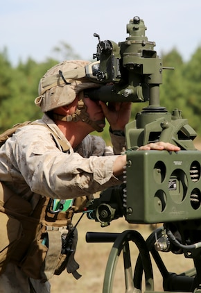 Sgt. James R. Nero, section chief of Gun 3, Battery A, Ground Combat Element Integrated Task Force, looks through the panoramic telescope of the M777A2 Lightweight Howitzer during a fire mission at Marine Corps Base Camp Lejeune, North Carolina, Oct. 29, 2014. Marines of Battery A conducted a live-fire artillery shoot, Oct. 28-30, 2014. From October 2014 to July 2015, the GCEITF will conduct individual and collective level skills training in designated ground combat arms occupational specialties in order to facilitate the standards based assessment of the physical performance of Marines in a simulated operating environment performing specific ground combat arms tasks. (U.S. Marine Corps photo by Sgt. Alicia R. Leaders/Released)