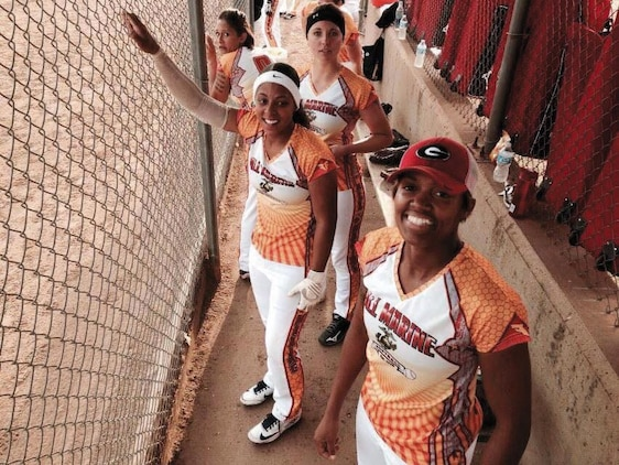 Sgt. Candice Clark (right) stands in the dugout with her All-Marine softball teammates Lance Cpl. Vanessa Crump (second right), Cpl. Rebecca Trimmer (third right) and Sgt. Aisha Shapiro-Kinghorn.