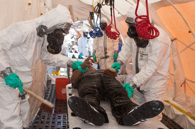 Chemical Support Unit members decontaminate a mock victim during a training exercise observed by Maj. Gen. H. Michael Edwards, the Adjutant General of Colorado, and other Colorado National Guard senior leaders and facilitated by the CONG Chemical, Biological, Radiological, and Nuclear (CBRN) Enhanced Response Force Package (CERFP) team at Maffaq Armor Base, Jordan, May 12, 2014. (Air National Guard photo by Capt. Darin Overstreet)