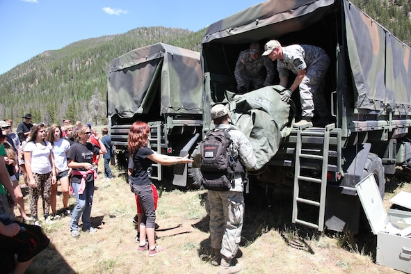 Teens line up to help unload tents and sleeping bags during the week-long Laramie River Valley Rendezvous program near Ft. Collins, Colo. July 6-12. The kids, who are identified as being high-risk for potential drug use, participate in various games and activities throughout the week and are mentored by members of the Colorado National Guard. (U.S. Air National Guard Photo by Tech. Sgt. B. Kevin Coulter)