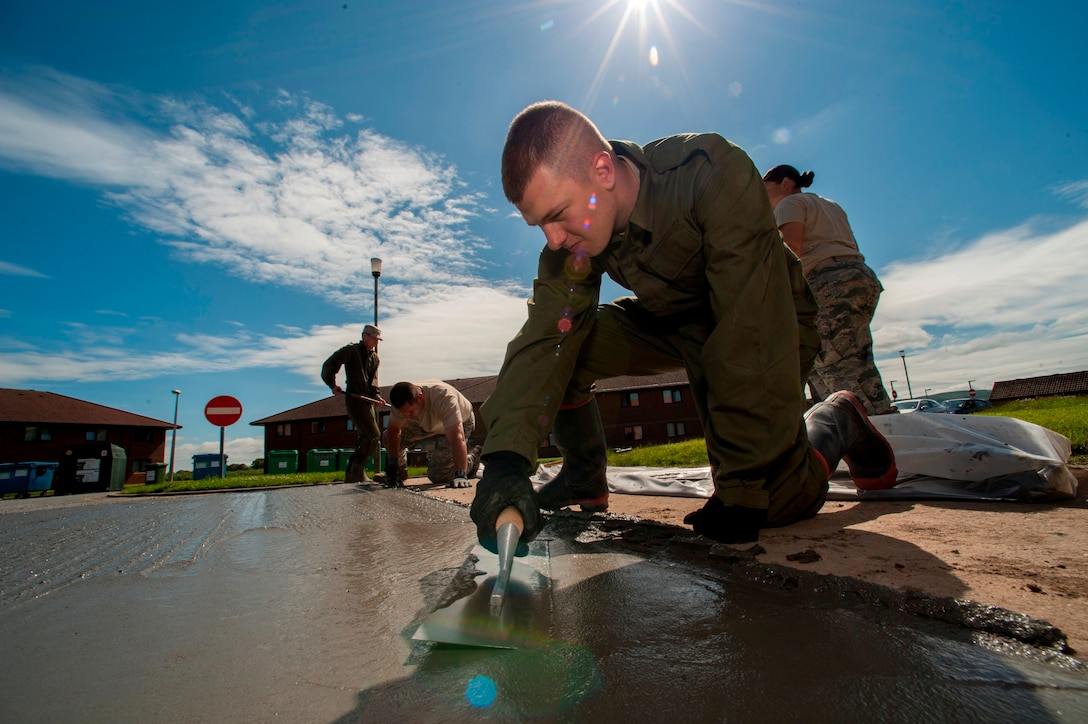 U.S. Air Force  Senior Airman Alexander Root-Davis, 140th Civil Engineer Squadron, Colorado Air National Guard, uses a finishing trowel to smooth out the top of freshly laid cement that will help improve the base junior dorms area once completed, during a deployed for training trip, known as Exercise Flying Rose at Kinloss Barrack in Forres, Moray, Scotland, United Kingdom, Jun. 16, 2014. Over 40 members of the 140th CES are in Scotland for their annual training and are accomplishing five construction projects that will improve several areas around Kinloss Barracks, during Exercise Flying Rose hosted by the British Army before returning back to Colorado later this month. (U.S. Air National Guard photo by Tech. Sgt. Wolfram M. Stumpf)