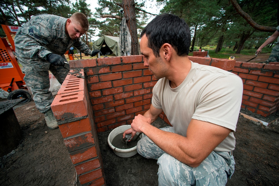 U.S. Air Force Senior Airman Justin Hoppe (left) and Staff Sgt. Tyson Bladassare, 140th Civil Engineer Squadron, Colorado Air National Guard, work on laying bricks on a new Barbecue Grill at a camp area, during a deployed for training trip, known as Exercise Flying Rose at Kinloss Barrack in Forres, Moray, Scotland, United Kingdom, Jun. 12, 2014. Over 40 members of the 140th CES are in Scotland for their annual training and are accomplishing five construction projects that will improve several areas around Kinloss Barracks, during Exercise Flying Rose hosted by the British Army before returning back to Colorado later this month. (U.S. Air National Guard photo byTech. Sgt. Wolfram M. Stumpf)