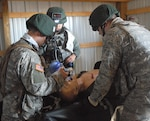 Fourth-year medical students work on a simulated patient presumed to be suffering from diabetic ketoacidosis, when the body has no insulin, as part of Operation Bushmaster, a field training exercise conducted at Fort Indiantown Gap, Pa. DoD photo by Sarah Marshall
